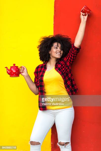 cheerful woman having fun with teapot and cup - red kettle stock photos and pictures