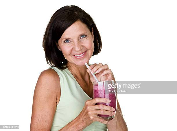 Cheerful woman holding a fruit smoothie
