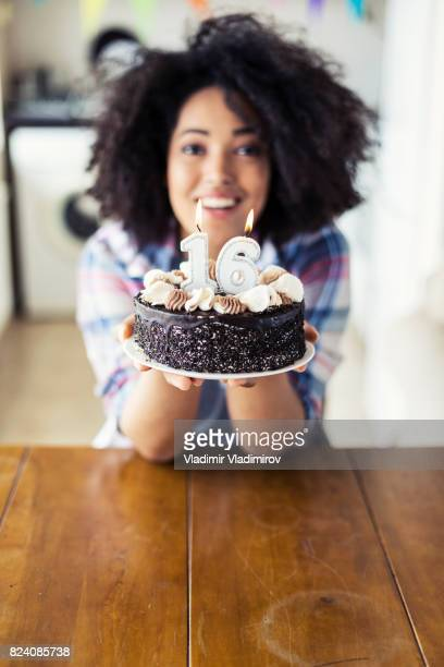 Cheerful woman holding birthday cake with candles