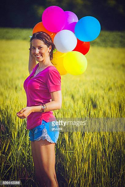 Cheerful woman holding colorful balloons, standing in the wheat field