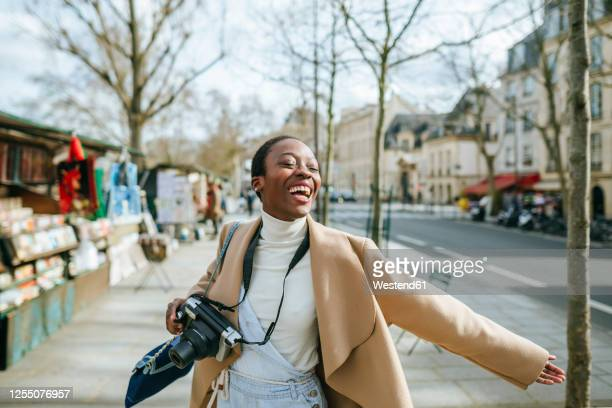 cheerful woman holding dslr camera on sidewalk in paris, france - one young woman only stock pictures, royalty-free photos & images