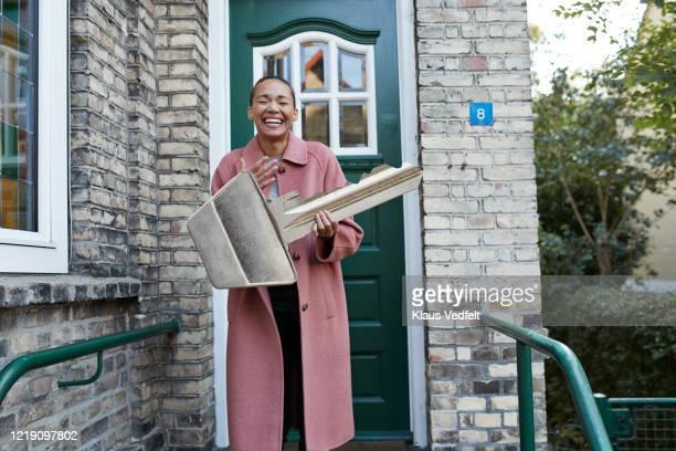 cheerful woman holding large key outside new house - surdimensionné photos et images de collection