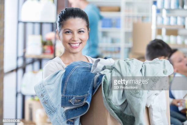 Cheerful woman holds box of donated clothing