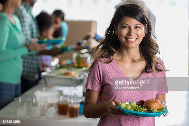 Cheerful woman holds plate of healthy food in soup kitchen