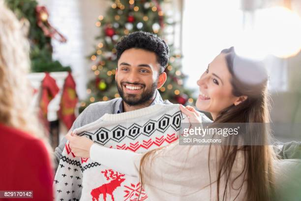 cheerful woman holds ugly christmas sweater up to her boyfriend - ugly asian woman stock photos and pictures