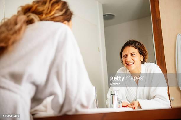 Cheerful woman in bathroom, washing her face
