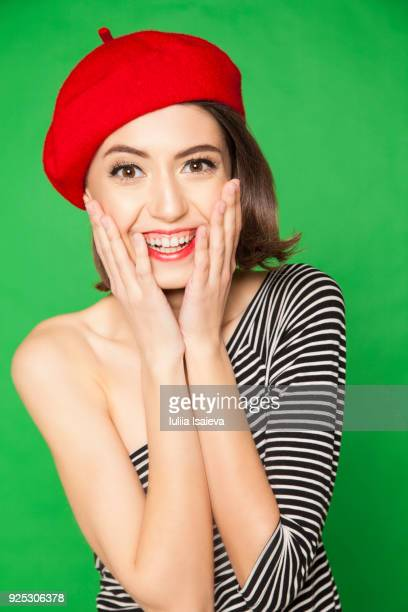 Cheerful woman in beret touching cheeks
