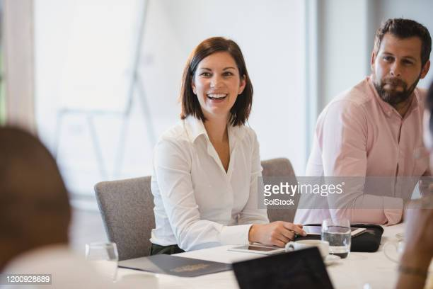 cheerful woman in business meeting with colleagues - real people stock pictures, royalty-free photos & images
