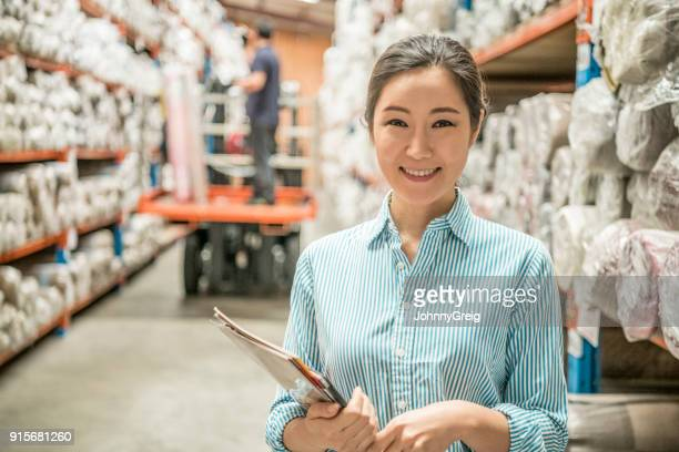 cheerful woman in carpet warehouse with paperwork smiling towards camera - korean ethnicity stock pictures, royalty-free photos & images