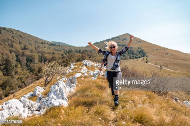 cheerful woman in mountain range - one mature woman only stock pictures, royalty-free photos & images