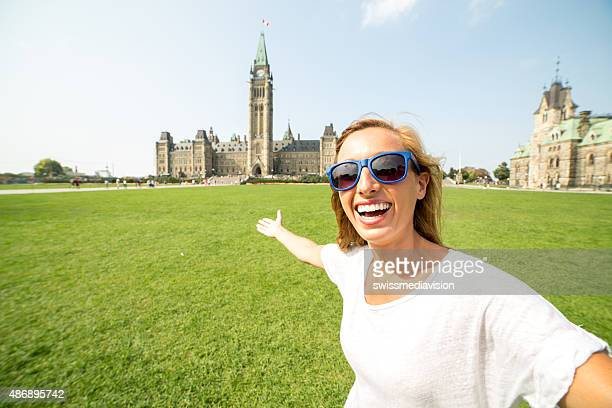 Cheerful woman in Ottawa taking selfie portrait with parliament house