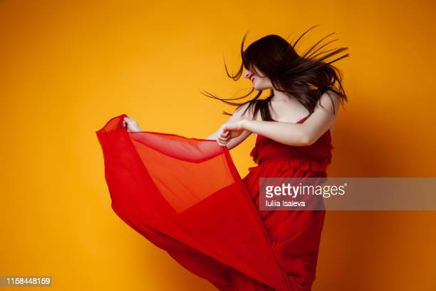 cheerful woman in red dress dancing - red dress stock pictures, royalty-free photos & images