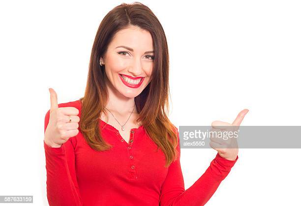 Cheerful woman in red shows thumbs up
