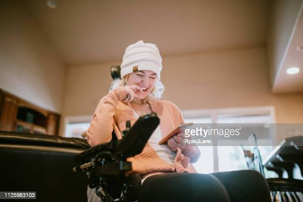 cheerful woman in wheelchair on smartphone at home - physical disability stock pictures, royalty-free photos & images