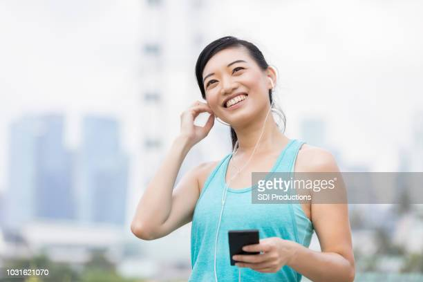 cheerful woman inserts earbuds before exercise - inserting stock pictures, royalty-free photos & images