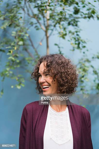 cheerful woman is looking away in back yard - mid adult woman sweater stock pictures, royalty-free photos & images