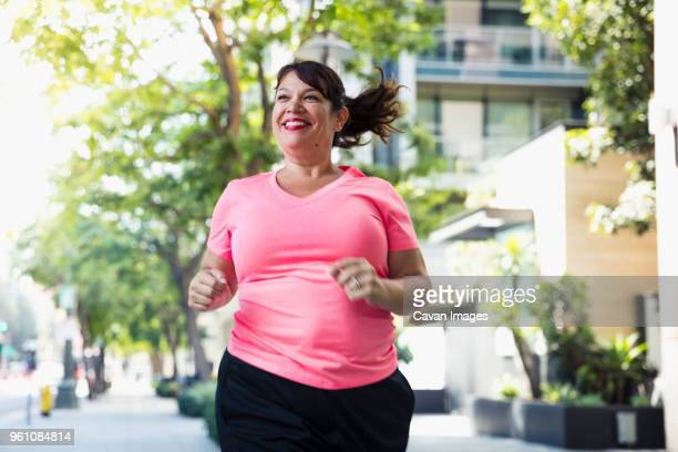 cheerful woman jogging on footpath in city - dikke vrouw stockfoto's en -beelden