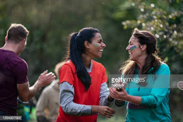 cheerful woman laughing and holding hands on cross country race - sporting term stock pictures, royalty-free photos & images