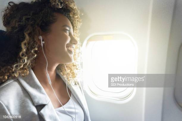 cheerful woman listens to music on airplane - staring stock pictures, royalty-free photos & images