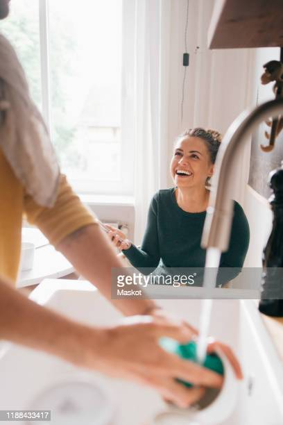 cheerful woman looking at boyfriend washing utensils at home - couples showering stock pictures, royalty-free photos & images