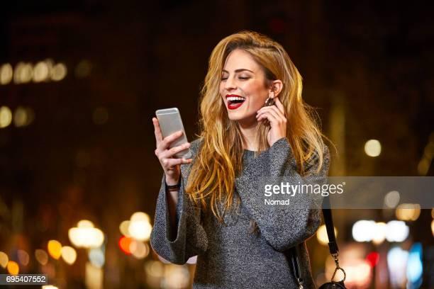 Femme joyeuse regarder téléphone mobile en ville