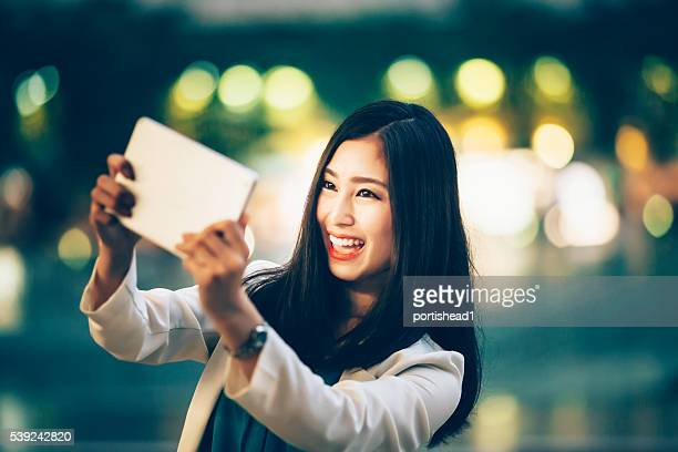 陽気な女性セルフィーを作るデジタルタブレットに ストリート