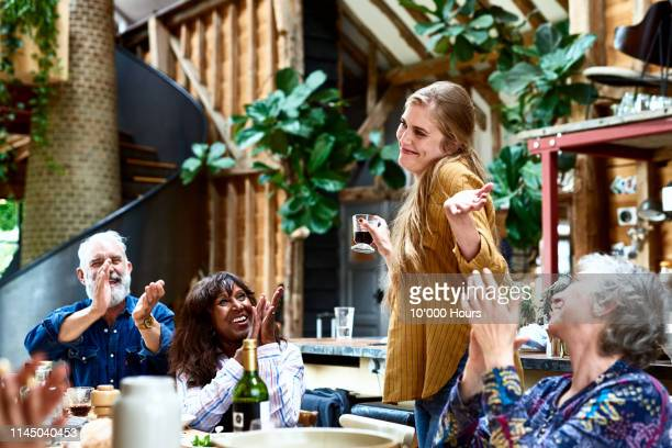 cheerful woman making speech at party smiling and shrugging - applauding stock pictures, royalty-free photos & images