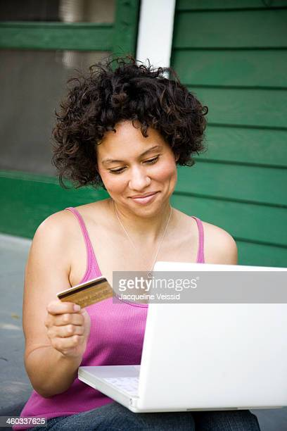 Cheerful woman on laptop holding credit card