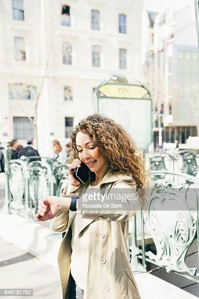 Femme heureuse vérifiant temps au téléphone à l'extérieur de la gare de métro