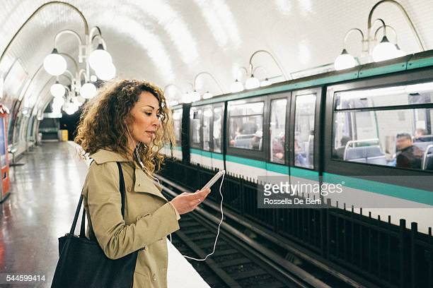 Cheerful woman on the phone, subway train on background