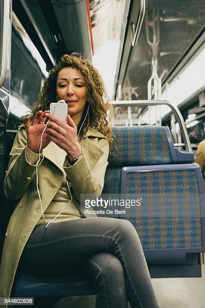 Femme heureuse au téléphone dans le métro voyage