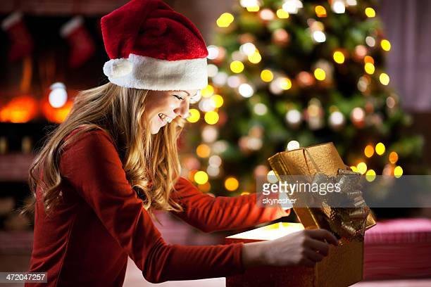 Cheerful woman opening Christmas presents.