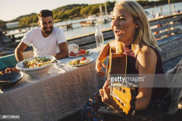 Cheerful woman playing guitar while friend sitting at picnic table on sunny day