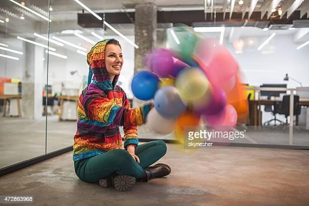 Mujer Alegre jugando con los coloridos globos en la oficina.
