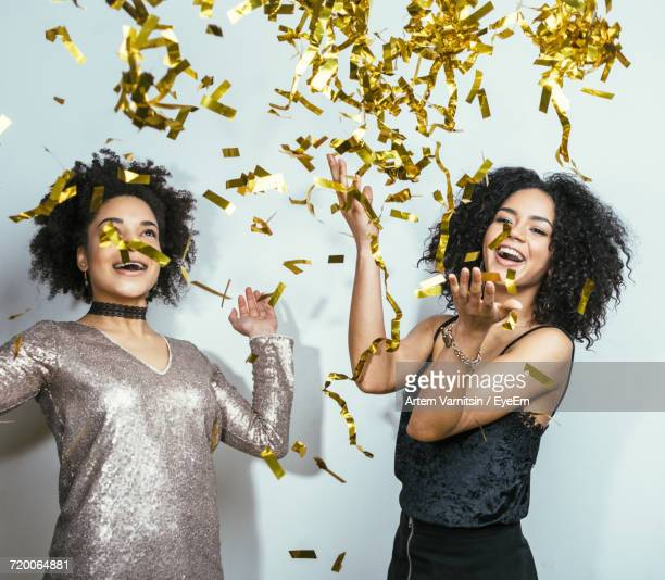 Cheerful Woman Playing With Confetti While Standing Against Wall