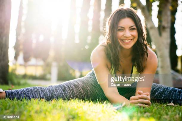 cheerful woman practicing yoga while exercising in park - benen gespreid stockfoto's en -beelden