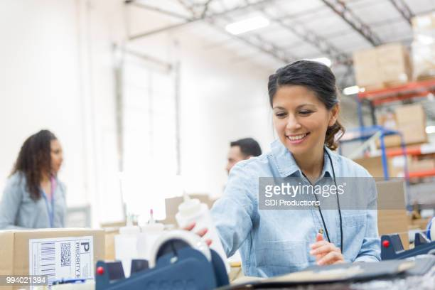 Cheerful woman prepares package in distribution warehouse