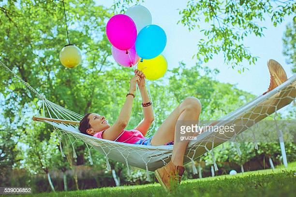 Freundliche Frau Entspannen Sie in einer Hängematte im Garten