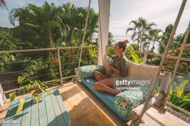 cheerful woman relaxing on patio over the jungle, thailand - eco tourism stock pictures, royalty-free photos & images