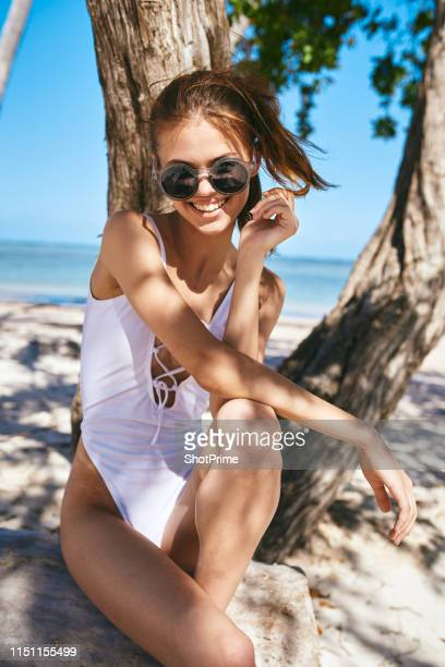 cheerful woman resting on the beach in a bathing suit and smiling - sexy figures stock pictures, royalty-free photos & images