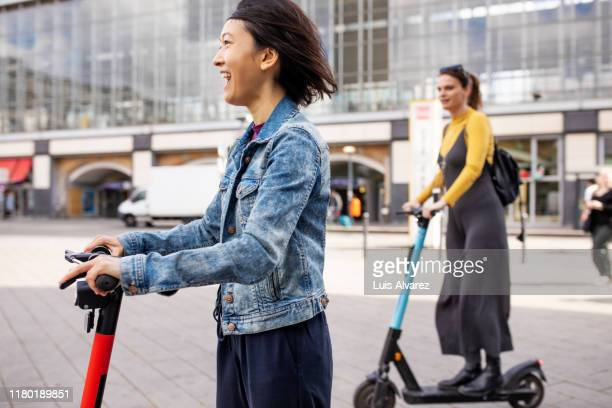 cheerful woman riding push scooter in city - tourismus stock-fotos und bilder