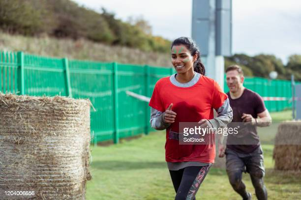 cheerful woman running outdoors in stampede race - fundraising stock pictures, royalty-free photos & images