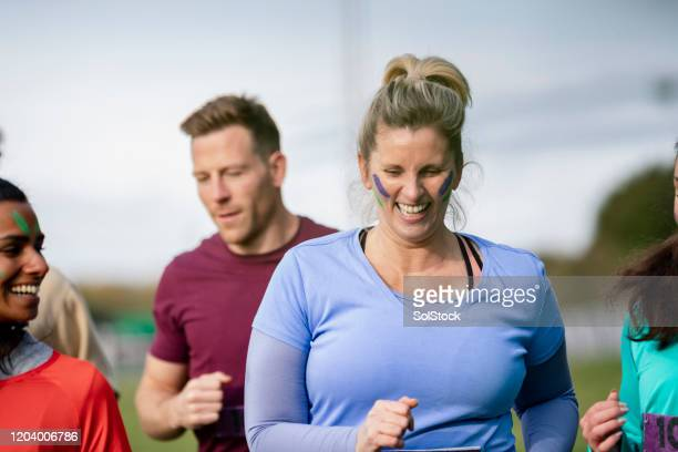 cheerful woman running with friends at outdoor charity event - competition group stock pictures, royalty-free photos & images