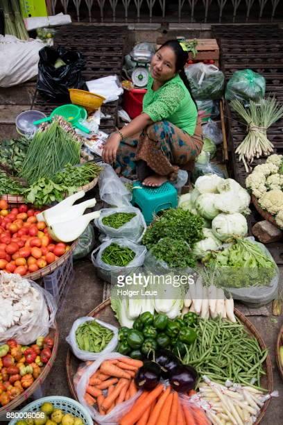 Cheerful woman sells vegetables at 18th Street Market in Chinatown, Yangon, Yangon, Myanmar