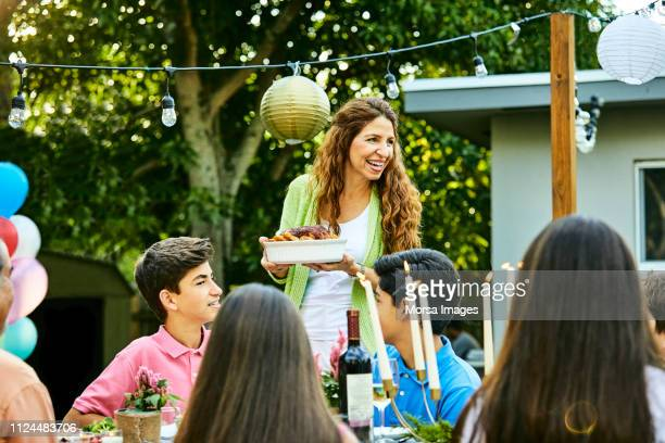 cheerful woman serving food to kids at back yard - serving food and drinks stock pictures, royalty-free photos & images