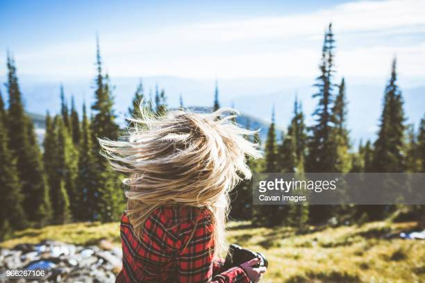 Cheerful woman shaking head while sitting in forest against sky on sunny day
