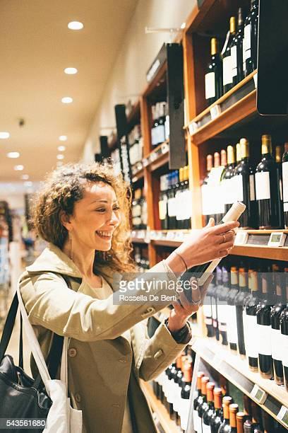 Mulher Alegre compras garrafa de vinho