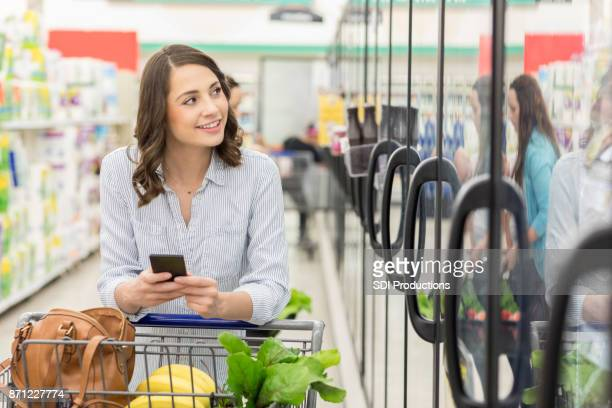 Cheerful woman shops in supermarket
