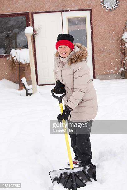 Fröhlich Frau shovelling Schnee Schneesturm