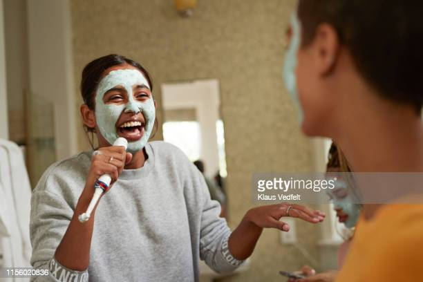 cheerful woman singing in front of female friend - electric toothbrush stock pictures, royalty-free photos & images
